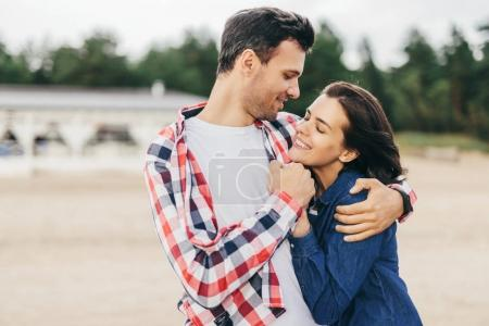 Cheerful woman and man embrace