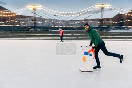 Portrait of happy middle aged male skater stands on ice ring, en