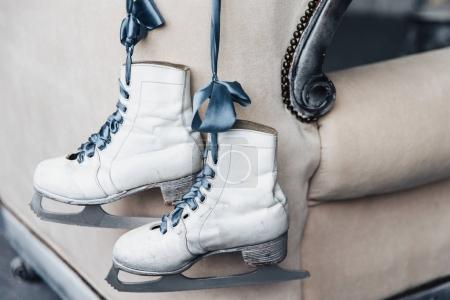 Photo of pair worn winter leather white skates for figure skating with shoelaces hang on ribbon. Used women`s skates of professional skater or ice hockey player