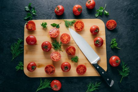Top view of red sliced tomatoes on wooden chopping board. Sharp knife near. Green parsley and dill. Dark background. Preparing fresh vegetable salad