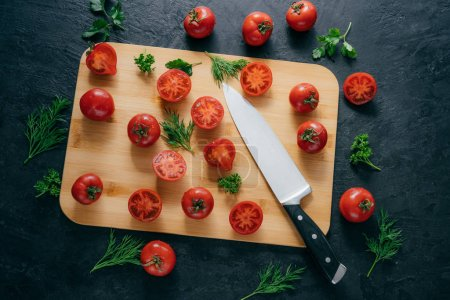 Cherry red tomatoes slices with knife on chopping board for making ketchup. Organic vegetables for making tasty full of vitamins salad. Vegetarian dish