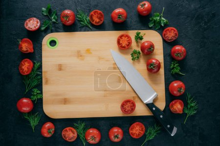 Tomatoes frame around wooden cutting board. Ripe vegetables and slice, green parsley and dill near kitchen board and knife. Food art