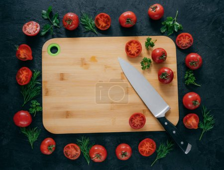 Horizontal top view of red tomatoes lying around wooden chopping board. Green parsley and dill. Knife near. Vegan table. Food concept