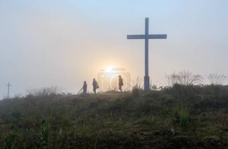 Foto de Nublado amanecer rocío en la montaña salvaje colina cubierta de hierba con cruces religiosas y familia caminando por pasar sobre el fondo del sol . - Imagen libre de derechos