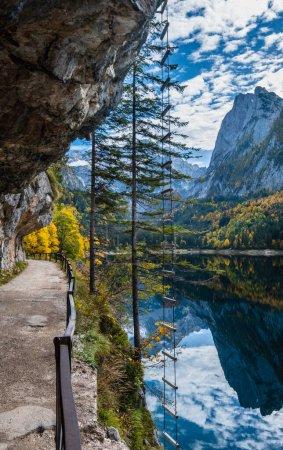 Photo pour Vue alpine d'automne. Lac de montagne paisible avec une eau claire et transparente et des reflets et escaliers ferrata. Gosauseen ou Vorderer Lac Gosausee, Haute-Autriche. Le sommet de Dachstein et le glacier loin. - image libre de droit