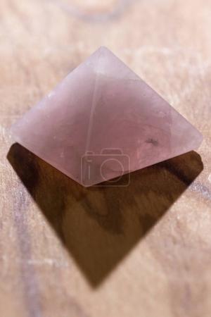 Photo pour Gros plan d'une pyramide de quartz rose sur un fond en bois, cette pierre est connue comme la pierre du coeur et favorise l'amour inconditionnel. - image libre de droit