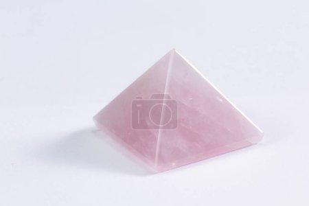 Photo pour Gros plan d'une pyramide de quartz rose sur fond blanc, cette pierre est connue comme la pierre du coeur et favorise l'amour inconditionnel. - image libre de droit