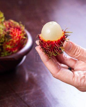 Photo pour Gros plan d'une main de femme tenant un rambutan qui a été coupé ouvert près d'un bol plus de ces délicieux fruits - image libre de droit