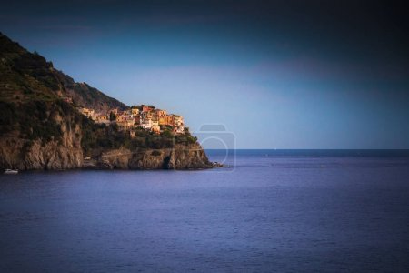 Manarola in Cinque Terre seen at dusk across the sea