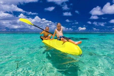 boys kayaking at tropical sea
