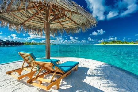 Two beach chairs under umbrella