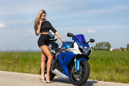 Portrait of a beautiful woman and a motorcycle of ...