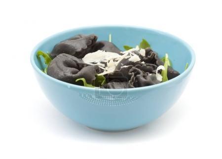 Photo pour Pâtes farcies Tortellini isolées avec des feuilles de salade de fusée et des copeaux de parmesan frais sur fond blanc - image libre de droit