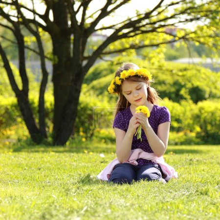 Photo for Adorable little girl with floral head wreath at the park - Royalty Free Image