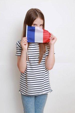 Photo for Lovely european little girl holding French flag - Royalty Free Image