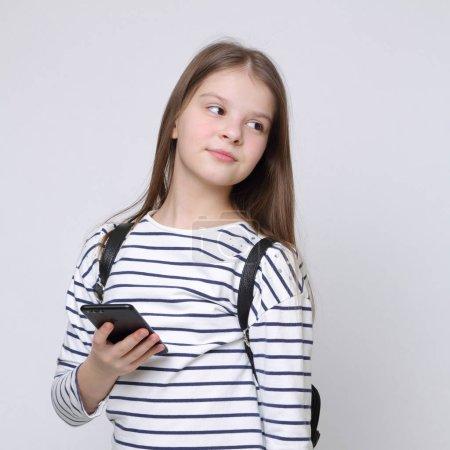 Photo pour Teen écolière tenue téléphone mobile (smartphone) - image libre de droit