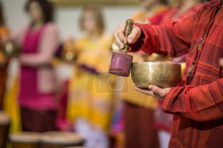 Photo for Man playing on a tibetian singing bowl (shallow DOF; color toned image) - Royalty Free Image