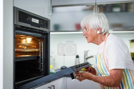 Senior woman/grandmother cooking in a modern kitch...