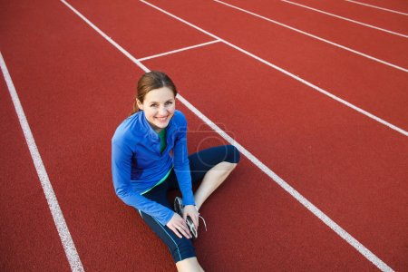 Photo for Pretty female runner stretching before her run at a track and field stadium - Royalty Free Image