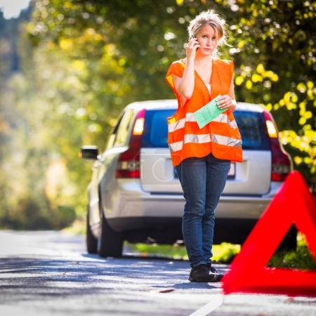 Photo for Young female driver wearing a high visibility vest, calling the roadside service/assistance after her car has broken down - Royalty Free Image