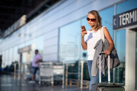 Photo pour Jeune femme avec ses bagages dans un aéroport international, après un atterrissage en toute sécurité, arrivée à destination, départ de l'aéroport, recherche d'un taxi - image libre de droit