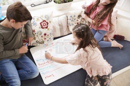 Children Making List Of Chores