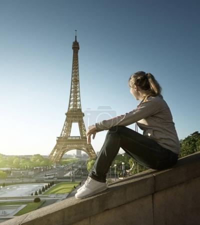 Girl looking at the Eiffel tower in sunrise time, ...