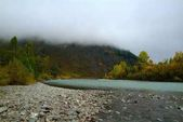 Morning fog over the Turquoise Katun with blue sky and beautiful forest