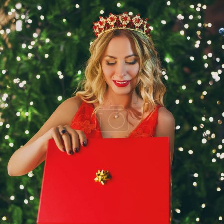 Blondy woman with gift box near Christmas tree