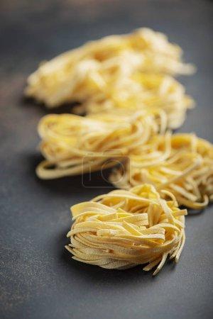 Photo pour Pâtes alimentaires italiennes crues traditionnelles tagliatelle, image sélective - image libre de droit