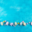 Easter eggs flat lay row on bright blue background...