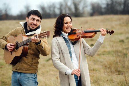 Photo for Beautiful woman in a coat playing violin next to a warmly dressed man playing guitar. They both having fun, laughter interrupts their music. Leafless trees and fields of dry grass surround them. - Royalty Free Image