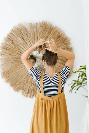 Photo pour Young woman in an ochre dress worn above striped shirt posing in front of mirror in a tropical style room. She's tending to her hear. - image libre de droit