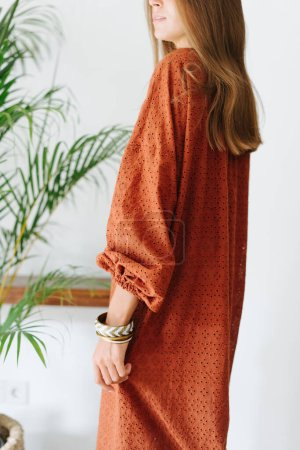 Photo pour Young pretty woman standing sideways in a dark orange maxi dress in a tropical style room. Cropped, half head. Open mouth and beautiful hair. - image libre de droit