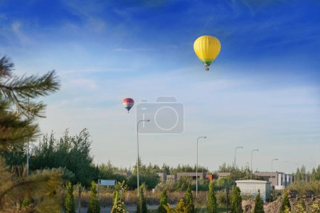 Two colorful hot air balloons flying in the suburbs