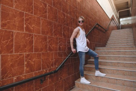Young hipster man posing standing on the stairs