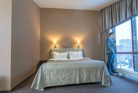Businessman talking on cell phone in hotel room
