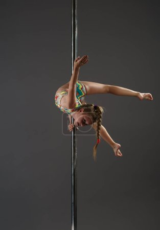 Junior girl balancing on pylon at dance studio
