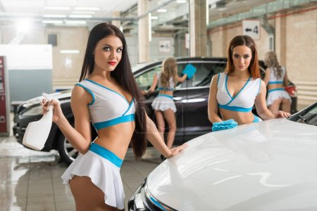 Sexy girls in formula one style posing at carwash