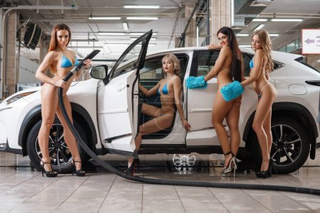 Several sexy girls in formula 1 style at carwash