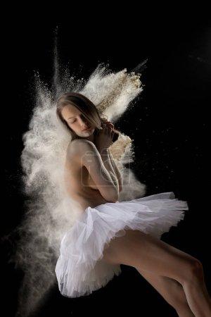 Photo pour Vue latérale d'une jeune femme seins nus en nuage de poudre blanche aux yeux fermés portant un tutu de ballet blanc sur fond noir en studio - image libre de droit
