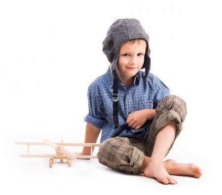 Photo for Little boy with pilot hat and toy airplane sitting isolated on white background - Royalty Free Image