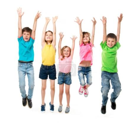 Photo for Beautiful children in colorful clothes jumping together with hands up isolated on white background - Royalty Free Image