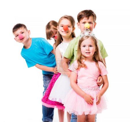 Photo pour Riant enfants avec clown nez debout un par un et se tenant l'un l'autre - image libre de droit