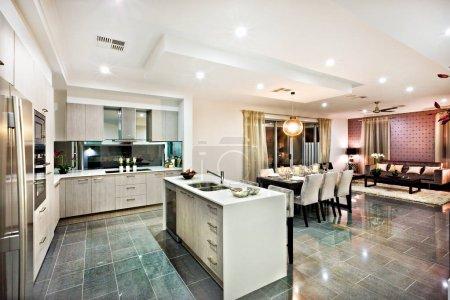 Photo pour Cuisine moderne et brillante avec salle à manger et salon, y compris un comptoir et des ustensiles de cuisine sur les carreaux réfléchissants, il y a des lumières clignotantes la nuit - image libre de droit