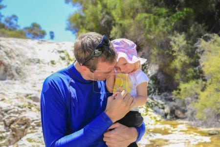 junger kaukasischer Mann im blauen Hemd hält seine kleine Tochter