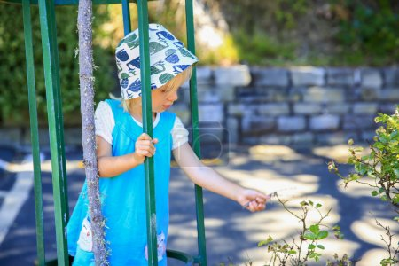 Little blond haired girl in a hat  is tyring bush leaves