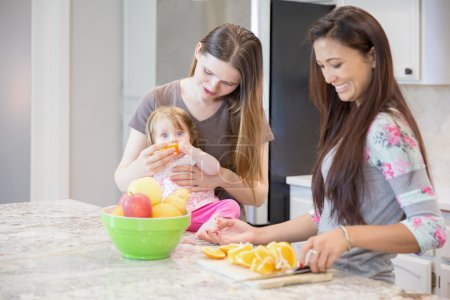 Two young women and little girl in the kitchen.