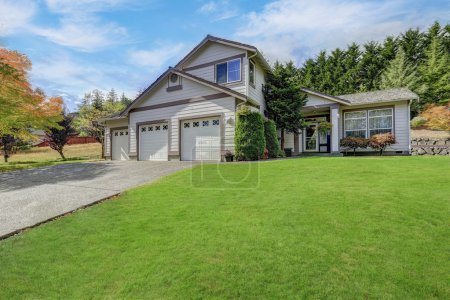Photo for Luxury house exterior with three garage spaces ,concrete driveway and well kept lawn in front of the house - Royalty Free Image
