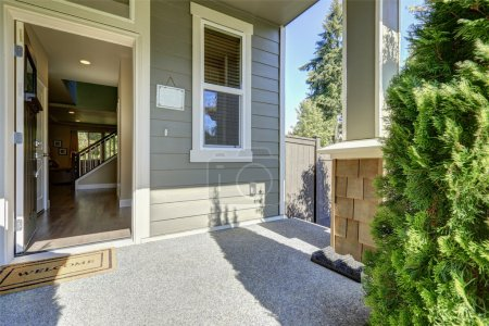 Photo for Entrance porch of American gray house with open front door with welcome mat on a sunny day. Northwest, USA - Royalty Free Image